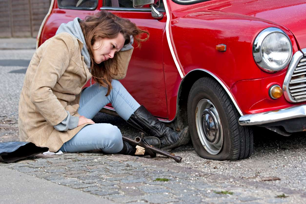 girl sitting on roadside with flat tyre