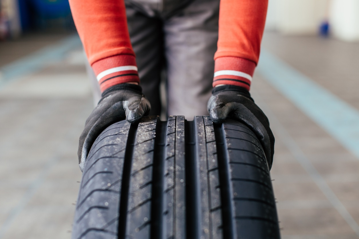 man wearing gloves rolling tyre with tread showing