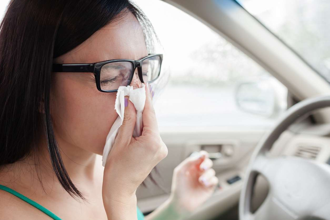woman sneezing in car